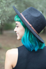 Smiling Young Woman With Dyed Blue And Green Hair Wearing Hat On Rainy Day