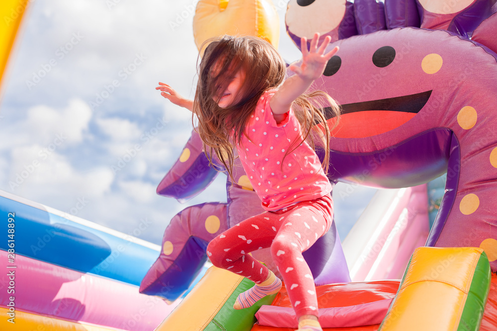 Fototapety, obrazy: A cheerful child plays in an inflatable castle