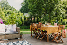 Dining Table Covered With Orange Tablecloth Standing On Wooden Terrace In Green Garden Prepared For Garden Party