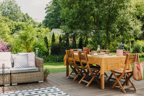 Leinwand Poster Dining table covered with orange tablecloth standing on wooden terrace in green