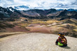 canvas print picture - Woman sitting at Rainbow Mountain hike in the Peruvian Andes near Cusco, Peru