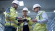 Three Heavy Industry Engineers Stand in Pipe Manufacturing Factory, Use Digital Tablet Computer, Have Discussion. Design and Construction of Large Oil, Gas and Fuels Transport Pipeline. Low Angle Arc