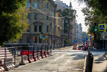 Repair Of A City Road On An Early Sunny Morning At An Empty Intersection In A Residential Area With Old Architecture. Working Traffic Lights And Fences In Pedestrian Areas