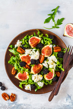 Salad With Figs, Feta Cheese And Blackberries In A Wooden Plate On White Background, Top View.