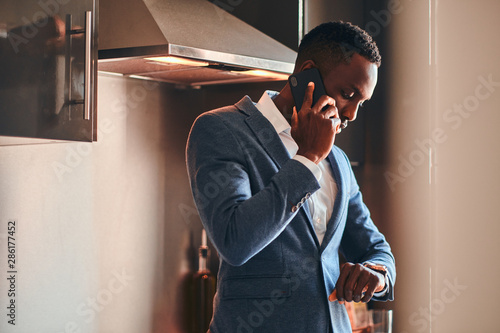 Fotografía  Young african man in white shirt is chatting by mobile phone at the kitchen