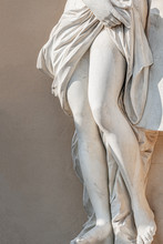 Statue Of Ancient Sensual Half Naked Renaissance Era Woman With Long Baked Legs In Potsdam At Smooth Wall Background, Germany
