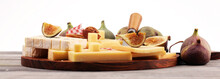 Cheese Platter With Different Cheese And Grapes And Figs And Nuts.