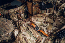 Still Life With Nice Watch And Military Uniform With Typical Camo Pattern.