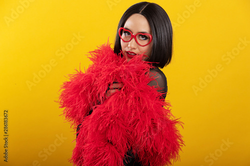 Portrait of pretty Asian woman wearing fluffy red feather boa Canvas Print