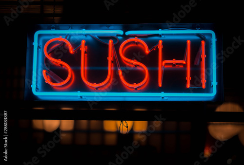 neon sushi sign outside of a restaurant