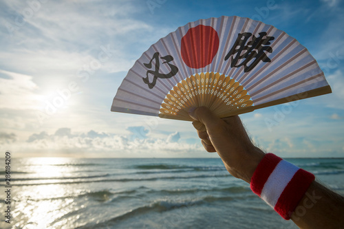 Hand of Japanese sports supporter holding a fan decorated with kanji characters spelling out hissho (English translation: certain victory) over a sunrise sea horizon