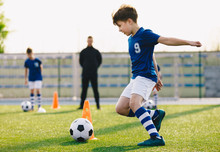 Children Training Football Dribbling In A Field. Kids Running The Ball. Players Develop Soccer Dribbling Skills. Boys Training With Balls And Cones. Soccer Slalom Drills