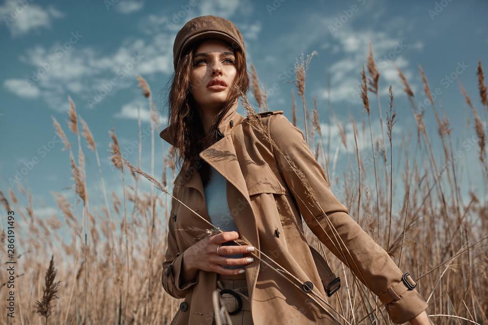 Fototapeta Beautiful Young Stylish Girl in Trench Coat Walking Autumn or Spring street. Autumn outdoor fashion.
