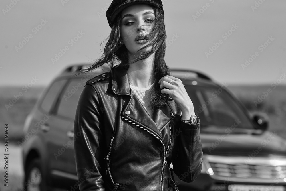Fototapeta High fashion portrait of brunette woman outside in leather black jacket and trendy hat. Outdoor fashion.