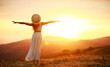 canvas print picture - Happy woman standing with her back on sunset in nature iwith open hands