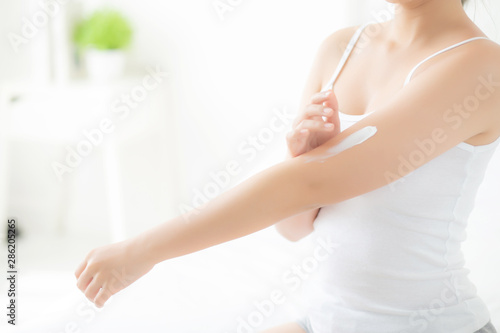 Beautiful portrait young asian woman smile applying sunscreen cream or lotion on skin care at bedroom, beauty asia girl using makeup and cosmetic for smooth and silky, wellness and health concept Canvas Print