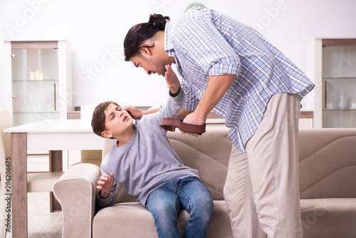 Canvas Print Father beating and punishing his sone