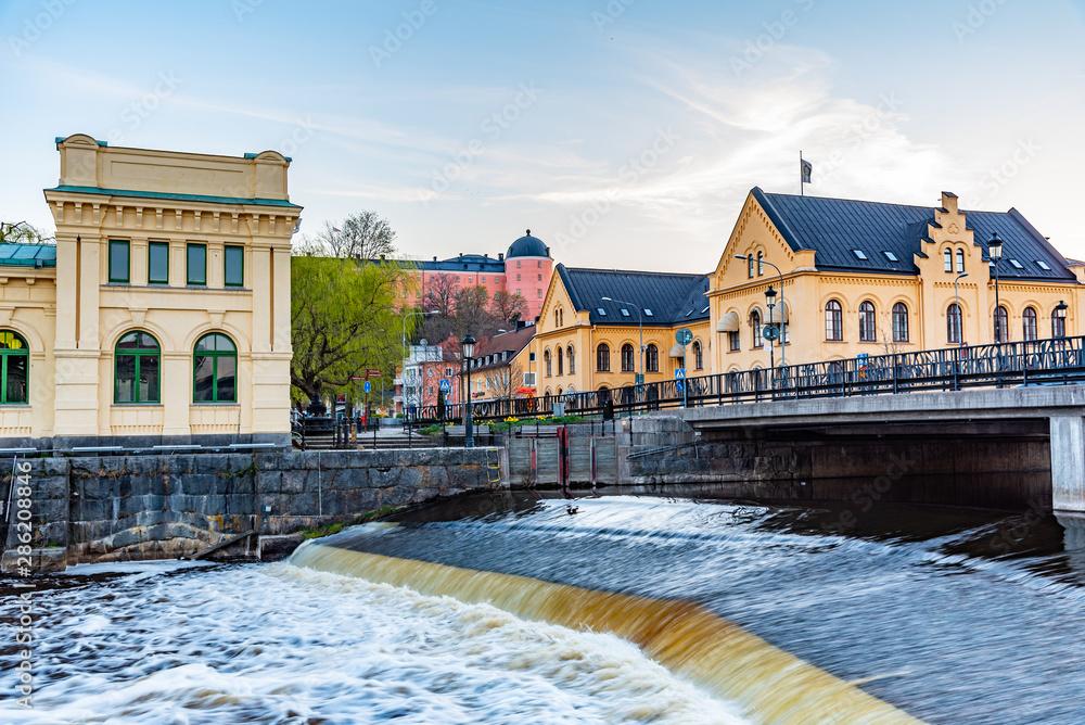 Obraz Sunset view of notable buildings alongside river Fyris in Uppsala, Sweden fototapeta, plakat