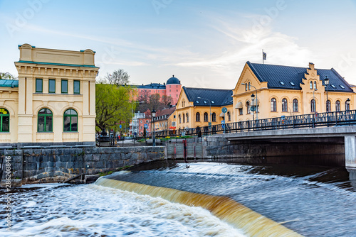 Sunset view of notable buildings alongside river Fyris in Uppsala, Sweden