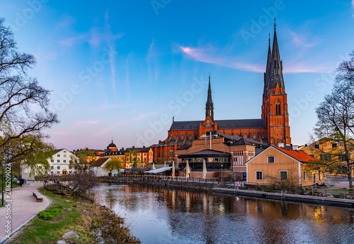 Tuinposter Oude gebouw Sunset view of Uppsala cathedral reflecting on river Fyris in Sweden