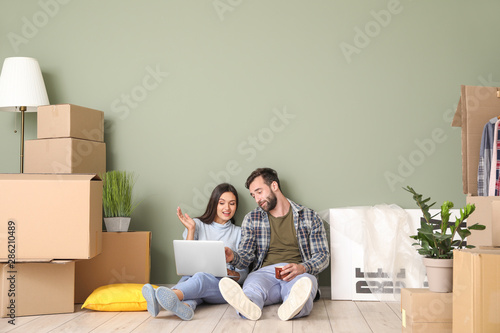 Fotografie, Obraz Young couple with cardboard boxes and laptop after moving into new house