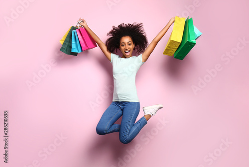 Fotografía  Portrait of jumping African-American woman with shopping bags on color backgroun