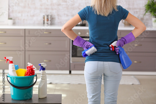 Fotomural  Woman with set of cleaning supplies in kitchen