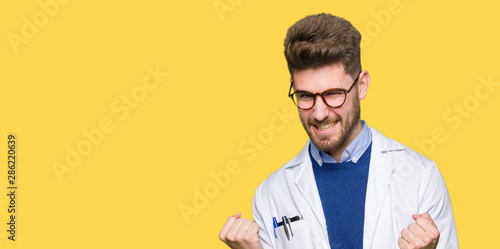 Fototapeta Young handsome scientist man wearing glasses very happy and excited doing winner gesture with arms raised, smiling and screaming for success