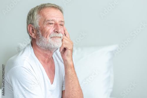 Stampa su Tela  Senior man sitting in bed, unhapppy pose.