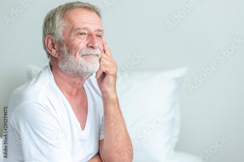 Senior man sitting in bed, thinking pose. Wallpaper Mural