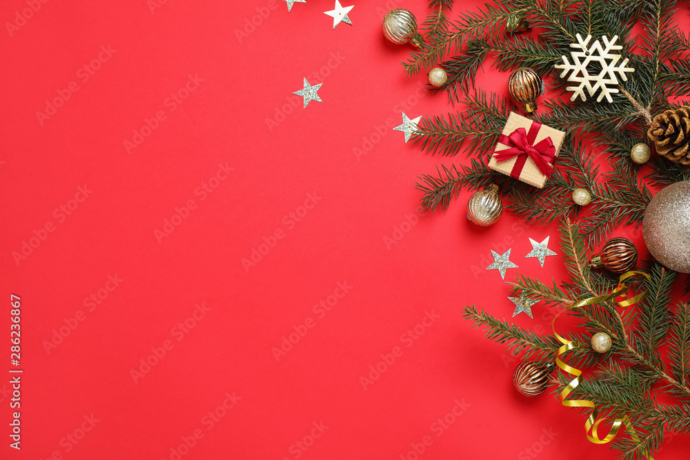 Fototapeta Fir branches with Christmas decoration on red background, flat lay. Space for text