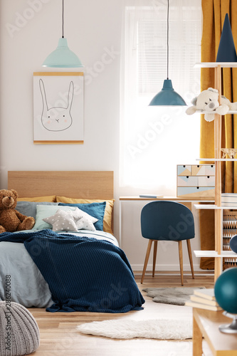 Poster Personal Teddy bear on single wooden bed in blue and orange bedroom interior