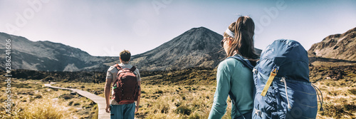 Fototapeta New Zealand Hiking Couple Backpackers Tramping At Tongariro National Park. Male and female hikers hiking by Mount Ngauruhoe. People living healthy active lifestyle outdoors obraz