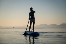Young Woman Paddling On A Sup Board