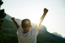 Young Child With Arms In The Air Welcoming Rising Sun