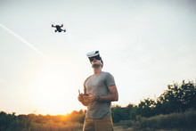 Drone Pilot. Man Using A Drone With Remote Controller And Virtual Reality Headset Making Photos And Videos On Sunset Field