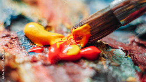 Obraz Creative artist using paintbrush to mix yellow and red oil paint on colorful palette. - fototapety do salonu
