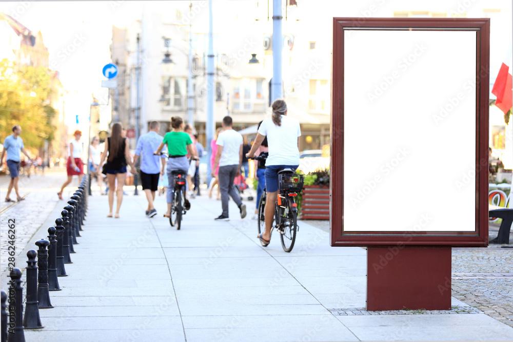 Obraz Bilbord reklamowy w centrum miasta Wrocław, w tle rowerzyści na rowerach. fototapeta, plakat