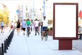 Fototapeta Miasto - Bilbord reklamowy w centrum miasta Wrocław, w tle rowerzyści na rowerach.
