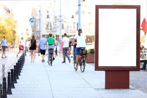 Bilbord reklamowy w centrum miasta Wrocław, w tle rowerzyści na rowerach. - fototapety na wymiar
