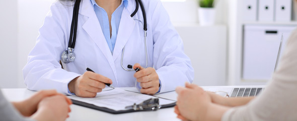 Doctor talking to patient at hospital office. Unknown physician says about medical exams results for choosing optimal treatment. Healthcare and medicine concept
