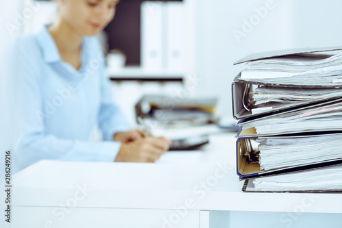 Fotografía  Binders with papers are waiting to be processed by business woman or bookkeeper back in blur