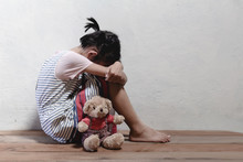 Traumatized Children Concept. Little Girl Sitting At The Corner Of The Room Feeling Sad And Lonely.