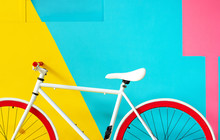 White Bike With Red Wheels. Parked Against Pastel Walls