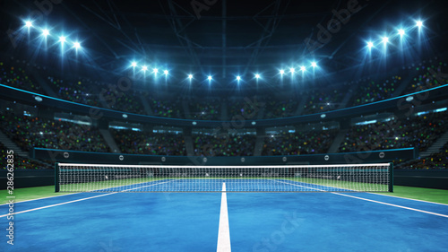 Blue tennis court and illuminated indoor arena with fans, player front view, pro Canvas Print