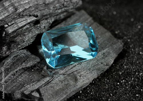 faceted blue jewelry gemstone aquamarine on black coal background Canvas Print