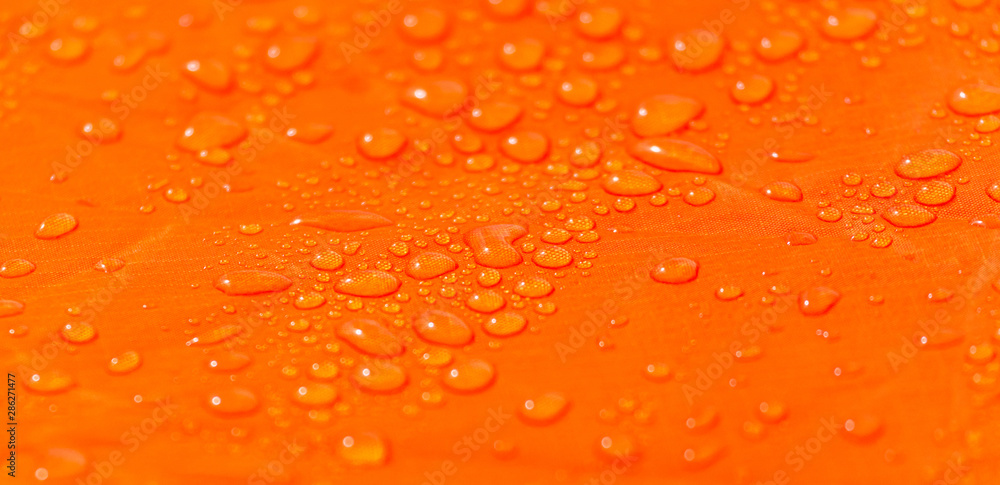 Fototapeta Raindrops on a tent of orange color as an abstract background