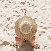 Summer Travel Fashion Concept. Beautiful Young, Tanned Woman With A Straw Hat Is Lying And Relaxing On Tropical Beach With White Sand. Top View, Flat Lay.