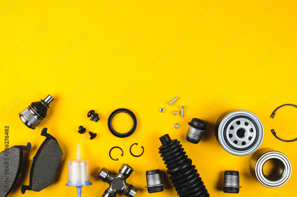 Fototapeta Set of car parts for maintenance on yellow background