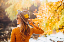 Blonde In A Yellow Jacket On A Background Of Autumn Nature. The Frame Is Lit By Sunlight. A Young Woman In A Gray Hat Looks At The Autumn Forest. Portrait Of A Woman In Autumn